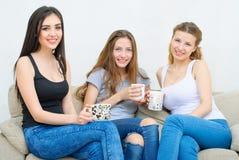 Tre amici felici che parlano e che bevono caffè o tè Fotografia Stock