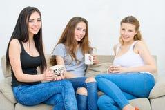 Tre amici felici che parlano e che bevono caffè o tè Immagini Stock Libere da Diritti