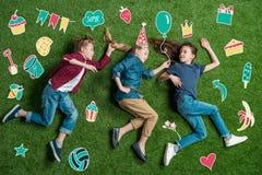 Tre amici felici che si trovano sull'erba Fotografia Stock Libera da Diritti