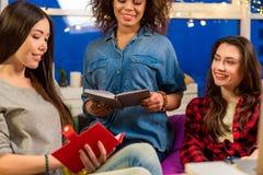 Tre amici felici delle donne che dicono in appartamento Immagini Stock Libere da Diritti