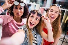 Tre amici femminili che prendono selfie che fa i fronti che alzano gli occhiali da sole in abbigliamento e sbocco degli accessori Fotografie Stock
