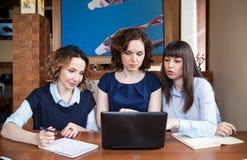Tre amici in un caffè che lavora ad un computer portatile Fotografia Stock Libera da Diritti