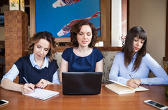 Tre amici in un caffè che lavora ad un computer portatile Fotografie Stock Libere da Diritti