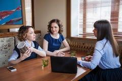 Tre amici in un caffè che lavora ad un computer portatile Immagine Stock