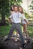 Tre amici in un giardino sull'oscillazione Immagine Stock