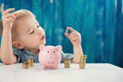 Tre anni del bambino che si siede st la tavola con soldi e un porcellino salvadanaio immagine stock