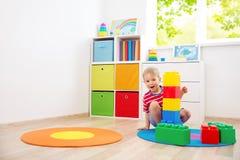 Tre anni del bambino che si siede sul pavimento con i cubi immagini stock libere da diritti
