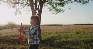 Tre anni del ragazzo che gioca con l'aeroplano alla bella vista della natura, tramonto archivi video