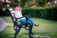 Tre anni del ragazzo che si siede sul banco in parco Fotografia Stock