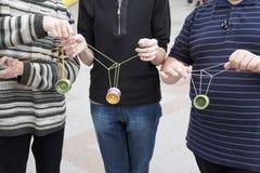 Tre anni dell'adolescenza con i giocattoli del yo-yo in loro mani Fotografia Stock Libera da Diritti