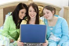Tre anni dell'adolescenza e un computer portatile fotografia stock