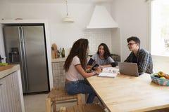 Tre anni dell'adolescenza parlano mentre studiano in una cucina facendo uso di un computer Immagine Stock