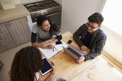 Tre anni dell'adolescenza studiano in cucina facendo uso dei computer, visualizzazione elevata Fotografie Stock