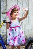 Tre anni della ragazza che invia i riguardi con una bicicletta Immagini Stock