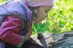 Tre anni della ragazza del bambino in età prescolare che soffia sulla lumaca commestibile strisciante Fotografia Stock