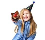 Tre anni di bambino della ragazza mangiano il muffin del dolce del cioccolato zuccherato con i frutti che celebra in cappuccio di Fotografia Stock