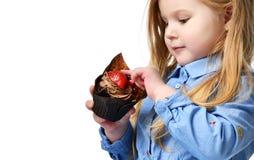 Tre anni di bambino della ragazza mangiano il muffin del dolce del cioccolato zuccherato con i frutti che celebra in cappuccio di Fotografie Stock