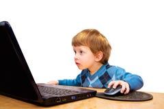 Tre anni svegli di ragazzo con il computer portatile isolato su bianco Immagini Stock