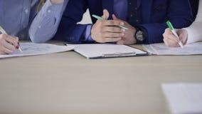 Tre anställda skriver sammanträde på tabellen inomhus lager videofilmer