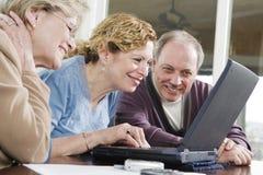 Tre anziani su un computer portatile Fotografia Stock