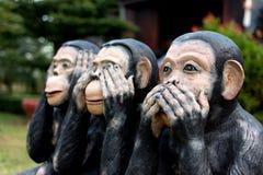 Tre apan, slut av små statyer för handen med begreppet av ser ingen ondska, hör ingen ondska och talar upp ingen ondska Arkivfoton