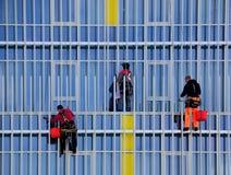 Tre arbetare som tvättar fönster arkivfoton