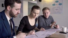 Tre arkitekter diskuterar bygga ritningar i deras kontor arkivfilmer