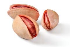 Tre arrostiti, pistacchi turchi salati e rossi isolati su fondo bianco immagini stock libere da diritti