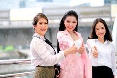 Tre asiatiska affärsflickor agerar med tummar upp för deras arbete och ler för att uttrycka av lyckligt under dagtid utanför royaltyfria bilder