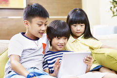 Tre asiatiska barn som tillsammans använder den digitala minnestavlan Royaltyfri Fotografi