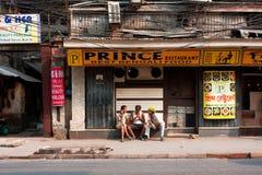 Tre asiatiska manar som talar nära den stängda restaurangen på den hoade dagen Royaltyfri Foto