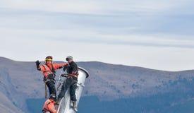 Tre assemblatori battentesi sotto l'elicottero immagini stock libere da diritti