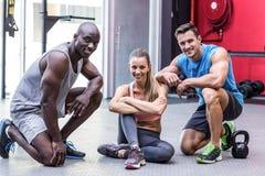 Tre atleti muscolari che sorridono alla macchina fotografica Fotografia Stock