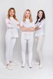 Tre attraktiva kvinnor i den vita ståenden på vit bakgrund royaltyfri bild
