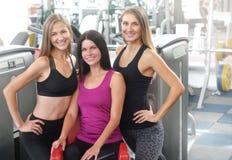 Tre attraktiva kvinnor i sportswearen som poserar i idrottshallen arkivbilder