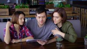Tre attraktiva ungdomari ett kafé eller en restaurang väljer en meny av drinkar och mat Vänner på fridagen kom till lager videofilmer