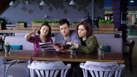 Tre attraktiva ungdomari ett kafé eller en restaurang väljer en meny av drinkar och mat Vänner på fridagen kom till stock video