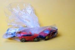 Tre automobili del giocattolo in una borsa trasparente di plastica su un fondo giallo immagine stock