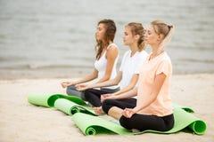 Tre avkopplade unga flickor sitter i lotusblommapositionerna med bokslut?gon som g?r yoga p? mats p? den sandiga stranden p? en v fotografering för bildbyråer