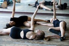 Tre ballerini di balletto sul pavimento durante la ripetizione Fotografie Stock