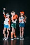 Tre bambini attivi in abiti sportivi che posano con l'attrezzatura di sport Immagini Stock Libere da Diritti