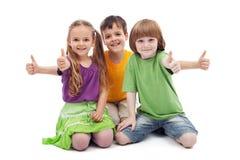 Tre bambini che danno i pollici aumentano il segno Immagine Stock