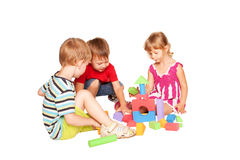 Tre bambini che giocano insieme e che costruiscono. Fotografia Stock