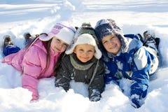 Tre bambini che giocano nella neve fresca Fotografia Stock Libera da Diritti