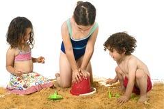 Tre bambini che giocano nella sabbia immagine stock libera da diritti