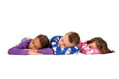 Tre bambini che indicano in loro pigiami caldi di inverno Immagine Stock