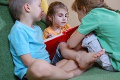 Tre bambini che leggono nel paese Fotografie Stock Libere da Diritti
