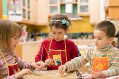 Tre bambini che modellano i biscotti da pasta Due ragazze e un ragazzo Fotografia Stock Libera da Diritti