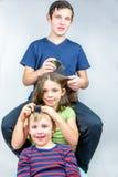Tre bambini che pettinano ogni altri si dirigono Trattamento efficiente dei pidocchi del capo, colpo del ritratto dello studio Immagine Stock