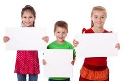 Tre bambini che si levano in piedi con lo spazio in bianco vuoto Immagini Stock